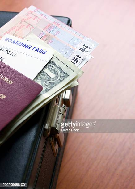 Passport, boarding pass, money and tickets on briefcase, close-up