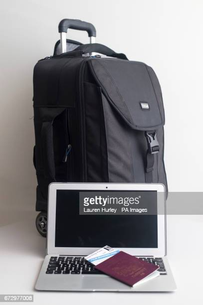A passport flight boarding pass and laptop next to a suitcase The UK and US have banned large electronic devices including laptops and tablets in...