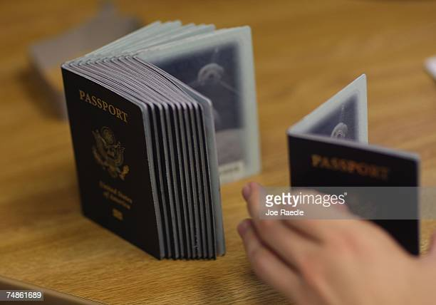Passport Processing employee uses a stack of blank passports to print a new one at the Miami Passport Agency June 22 2007 in Miami Florida The Bush...