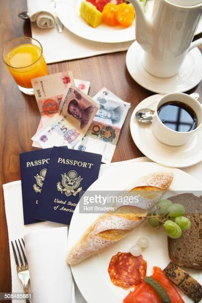 Passports, money and food on breakfast table