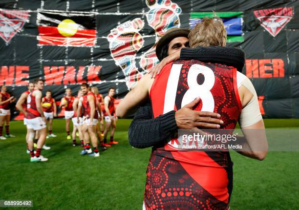 Past Bombers indigenous player Aaron Davey hugs Michael Hurley of the Bombers during the 2017 AFL round 10 Dreamtime at the G match between the...