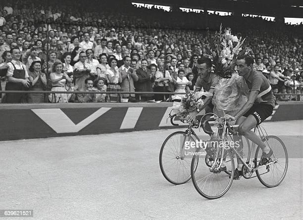 Past champions of the Tour de France French Louison Bobet and Italian Fausto Coppi complete an honorary lap around the Parc des Princes after...