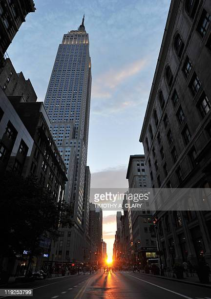 Past the Empire State Building the sun sets along 34th Street aligning with the Manhattan street grid during 'Manhattanhenge' July 13 2011 in New...