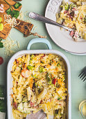 Pasta casserole with romanesco cabbage and ham in creamy sauce,  served in plate with fork on kitchen table with ingredients, top view, close up.  Italian cuisine