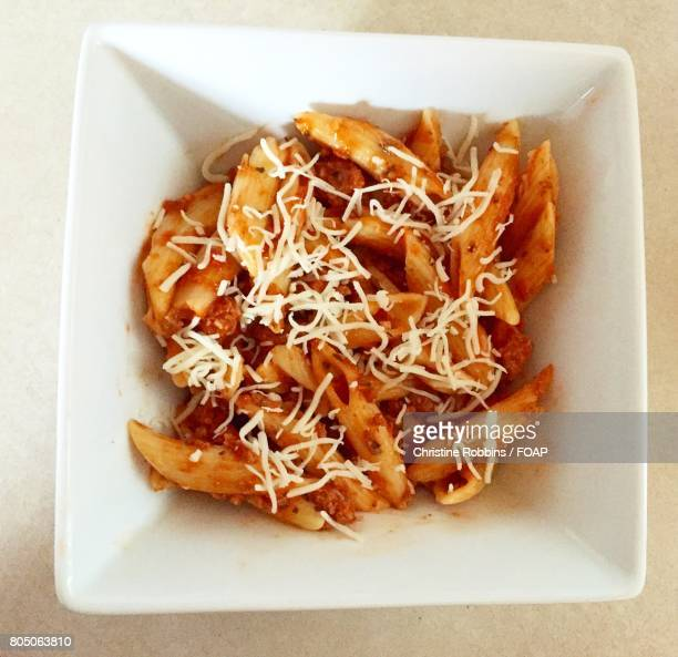 Pasta garnished with cheese in bowl