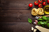 Ingredients for cooking traditional italian pasta shot on rustic wood table. The ingredient are paced at the right side of the frame leaving a useful copy space at the center-left side. Composition in