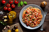 Pasta with tomato sauce shot from above on rustic wood table. Some ingredients for cooking pasta like tomatoes, olive oil, basil, parmesan cheese and a pepper mill are around the plate. DSRL low key s