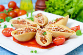 pasta shells stuffed with minced beef meat with herbs and tomato sauce on a plate