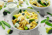 Pasta with green vegetables broccoli, Mange tout and creamy sauce in white plate.