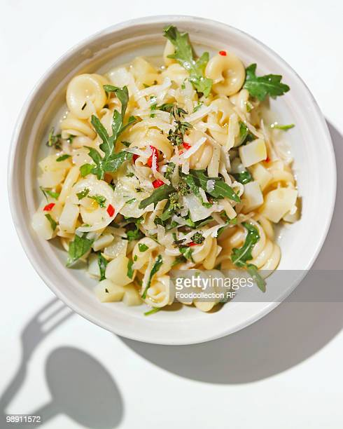 Pasta with potatoes and rocket in bowl, close-up