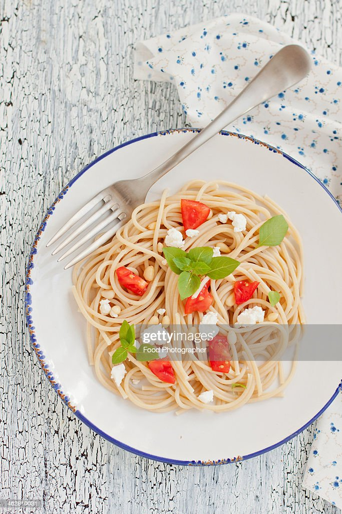 Pasta with tomatoes, basil, feta and pine nuts : Stock Photo