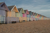 A row of pastel beach huts at Mersea Island, Essex, UK