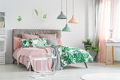 Pastel beddings on stylish bed in white bedroom with plants