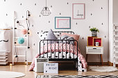 White ladder with pompons next to bed with shaped pillow in pastel child's bedroom with rugs