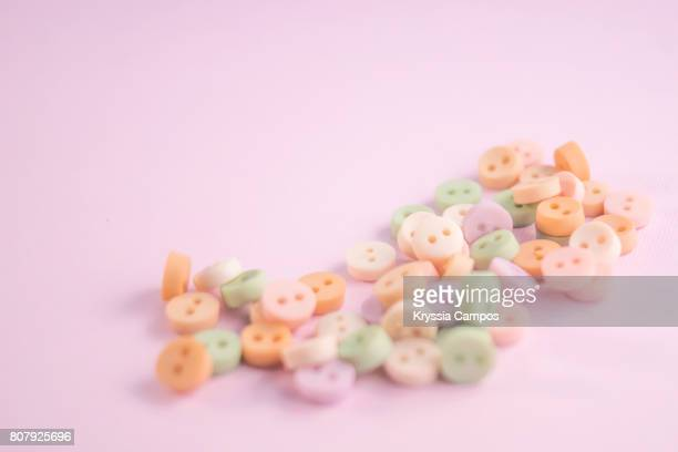 Pastel Colored Buttons on Pink Paper Background