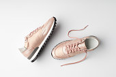 Pastel pink female sneakers on white background. Flat lay, top view minimal background.