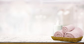 Pastel pink towels in basket on top wood table with copy space on blurred bathroom background. Copy space for Products Display Concept.
