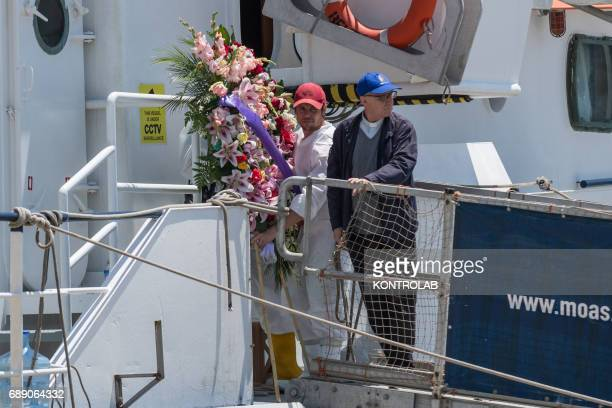 A pastor and a volunteer bring a crown of flowers to the dead at sea during the phase of landing migrants from Phoenix MOAS ship in the port of...