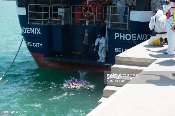 A pastor and a volunteer launch a wreath of flowers for the dead at sea during the phase of landing migrants from Phoenix MOAS ship in the port of...