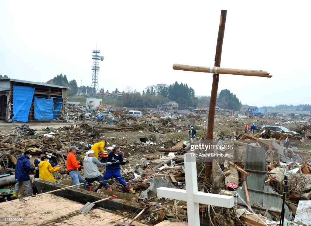 A pastor and volunteer workers clear the debris around the cross made by logs washed away by the tsunami at the place where the Kesennuma Daiichi Bible Baptist Church used to stand on May 1, 2011 in Kesennuma, Miyagi, Japan. The government's construction of temporary housing in areas devastated by the March 11 magnitude 9.0 earthquake and tsunami continues as many residents remain in temporary evacuation shelters.