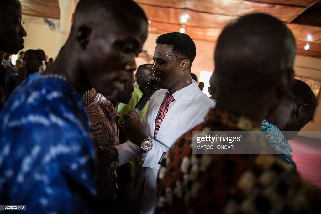 Pastor Antony Najb greets worshippers as they leave after the Sunday's service at the Winners Chapel International in the Weasay district of Monrovia on May 1, 2016. / AFP / MARCO