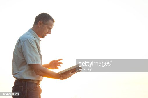 Pastor casually dressed walking in sunlight reading Bible