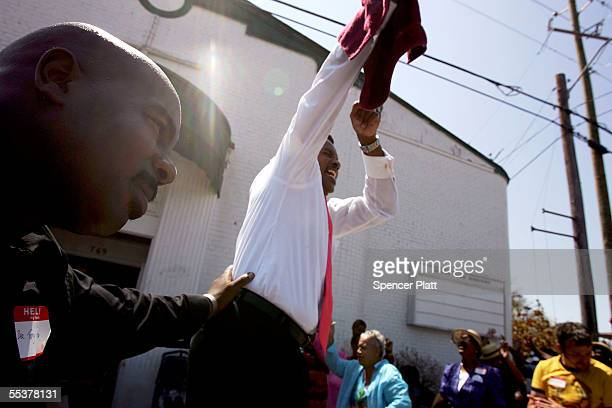 Pastor Debruce Nelson leads a Sunday service outside of the Lighthouse Apostolic Church which was damaged by Hurricane Katrina September 11 2005 in...