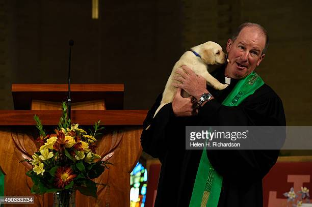 Pastor Reverend Dr John Bell holding his 7 week old puppy Magnolia leads members in the congregation in the Blessing of the Animals at Wellshire...