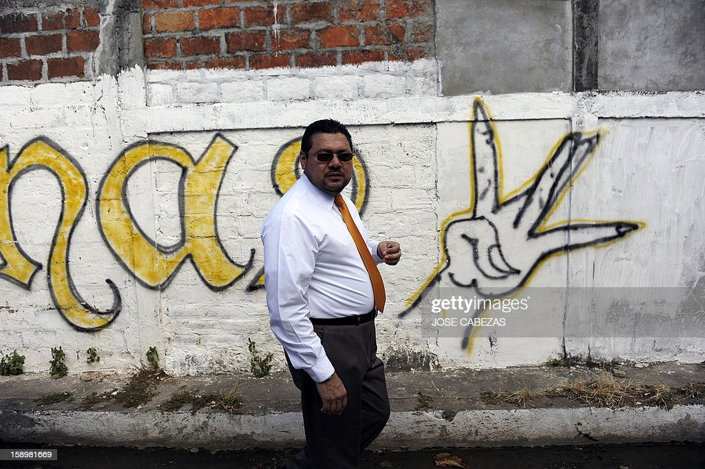 A pastor walks past a 'Mara Maquina' gang graffiti at Chintu neighborhood in Apopa, 14 km north of San Salvador, El Salvador on January 4, 2013. Graffitis started to be erased as Raul Mijango, Gang truce mediator, announced that 18 districs in El Salvador will be considered 'Sanctuary Territories' for gangs as a second stage of the gang truce. AFP PHOTO/ Jose CABEZAS