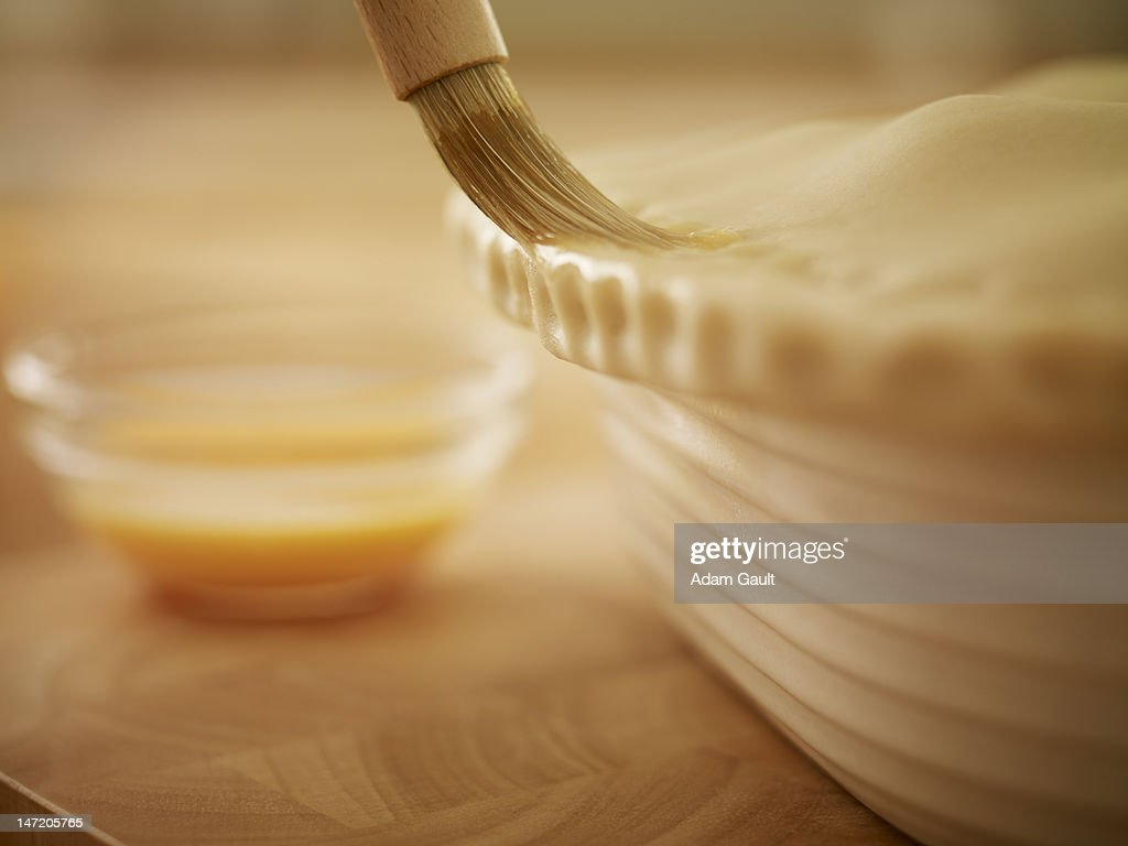 Pastry being brushed with egg wash : Stock Photo