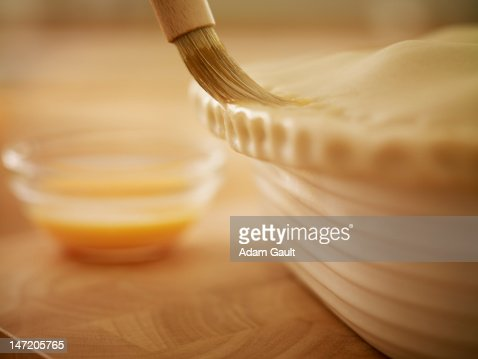 Pastry being brushed with egg wash