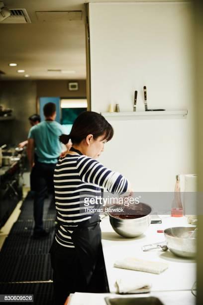 Pastry chef preparing chocolate for dessert in restaurant kitchen