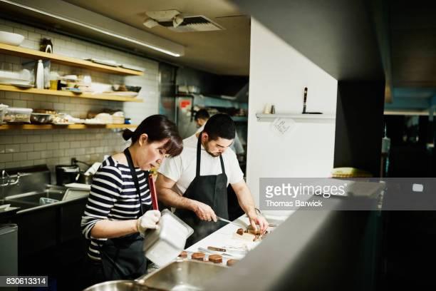 Pastry chefs preparing desserts for dinner service in restaurant kitchen