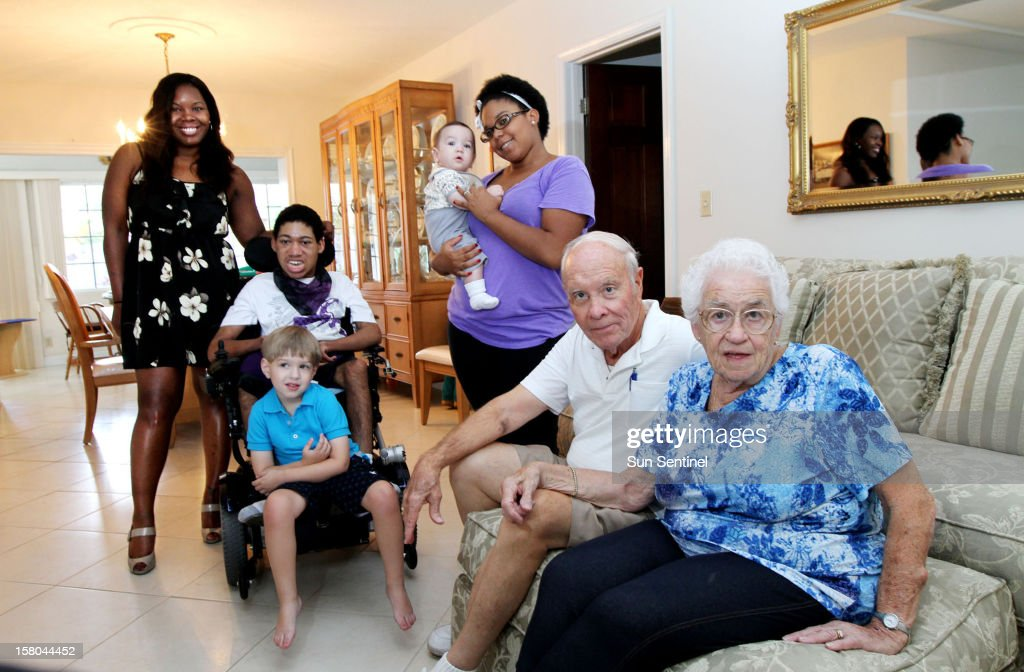 Pat (far right) and Bill Meyers (second from right) in their living room with their adopted and fostered children at their home in Fort Lauderdale, Florida, November 21, 2012. From left is adopted daughter Sheila Meyers, 32, foster child Kevin Mike, 17, adopted Alejandro, 4, foster child Gianni, 6-months, adopted daughter Megan Meyers, 24. Bill and Pat, who are both 78 years old, have fostered more than 250 children for over 45 years.