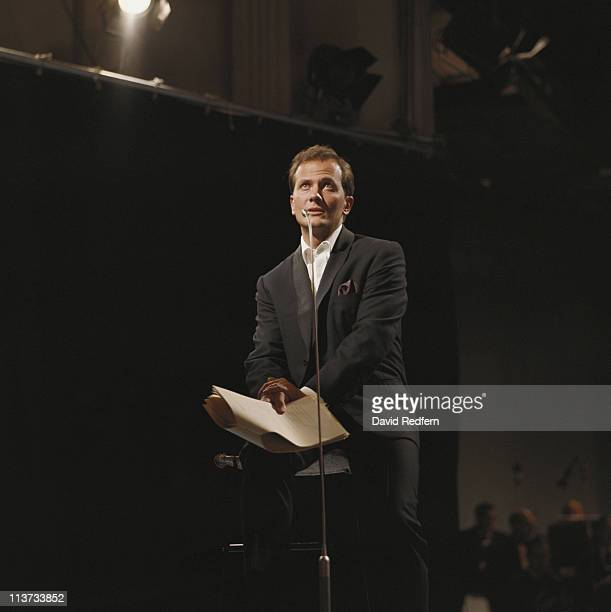 Pat Boone US singer sits singing into a microphone during a live concert performance circa 1965 Boone is holding sheets of paper in his hand