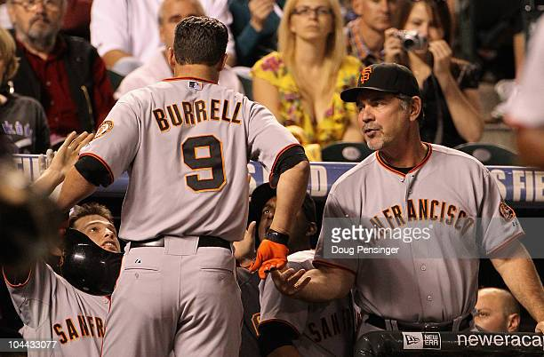 Pat Burrell of the San Francisco Giants is welcomed back to the dugout by manager Bruce Bochy and his teammates after his game winning two run home...