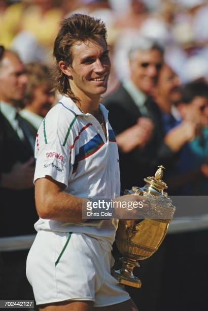 Pat Cash of Australia holds aloft the Gentlemen's Singles Trophy after winning the Men's Singles Final against Ivan Lendl at the Wimbledon Lawn...
