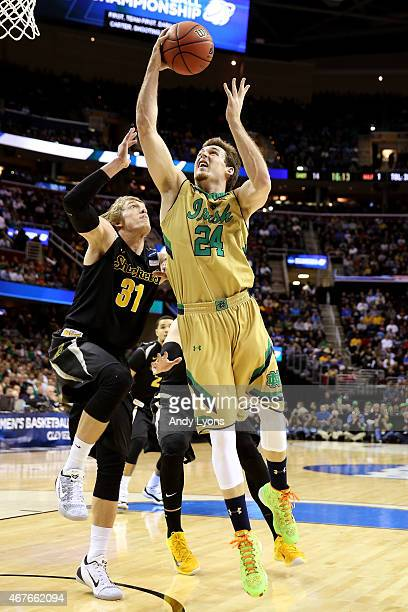Pat Connaughton of the Notre Dame Fighting Irish drives to the basket against Ron Baker of the Wichita State Shockers in the first half during the...