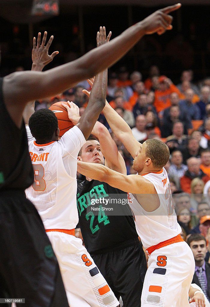 Pat Connaughton #24 of the Notre Dame Fighting Irish looks to pass the ball through traffic against Jerami Grant #3 and Brandon Triche #20 of the Syracuse Orange during the game at the Carrier Dome on February 4, 2013 in Syracuse, New York.