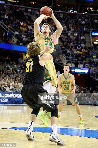 Pat Connaughton of the Notre Dame Fighting Irish shoots over Ron Baker of the Wichita State Shockers in the first half during the Midwest Regional...