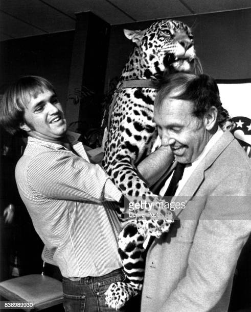 Pat Craig of the Boulder Zooalogical preserve holds Jaguar 'Black Gold' who is busy licking to top of the head of Denver Gold owner Rob Blanding...