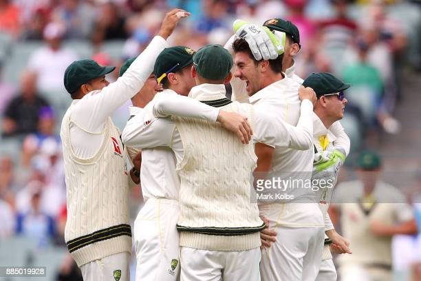 Pat Cummins of Australia celebrates with his team after taking the wicket of Joe Root of England during day three of the Second Test match during the...