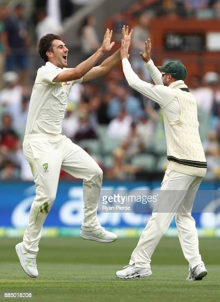 Pat Cummins of Australia celebrates with Nathan Lyon of Australia after claiming the wicket of Joe Root of England during day three of the Second...
