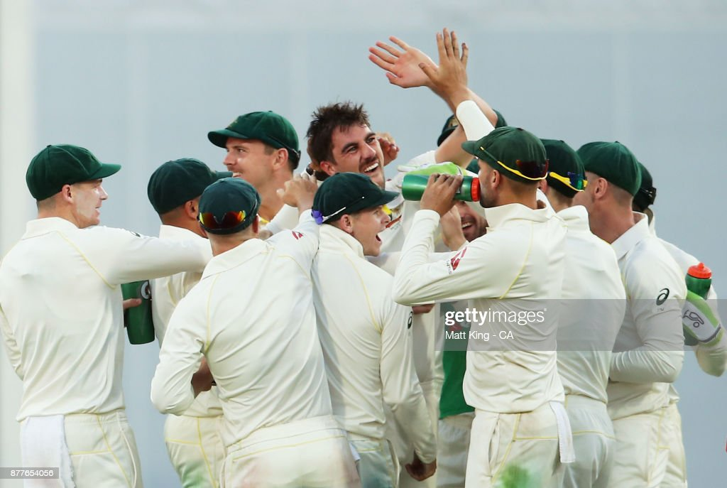 Pat Cummins of Australia celebrates with team mates after taking the wicket of Joe Root of England during day one of the First Test Match of the 2017/18 Ashes Series between Australia and England at The Gabba on November 23, 2017 in Brisbane, Australia.