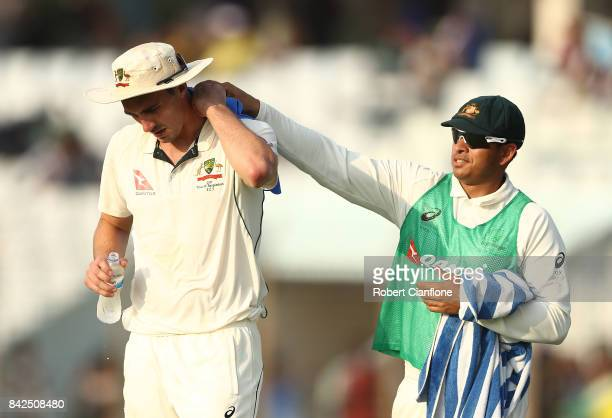 Pat Cummins of Australia is given a cold towel by Usman Khawaja of Australia during day one of the Second Test match between Bangladesh and Australia...
