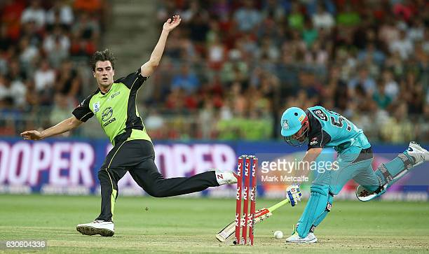 Pat Cummins of the Thunder attempts to run out Chris Lynn of the Heat by kicking the ball at the stumps during the Big Bash League match between the...