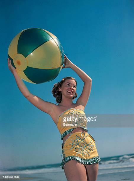 Pat Hall is wearing a 'twopiece' bathing suit in this photo while playing with a beach ball