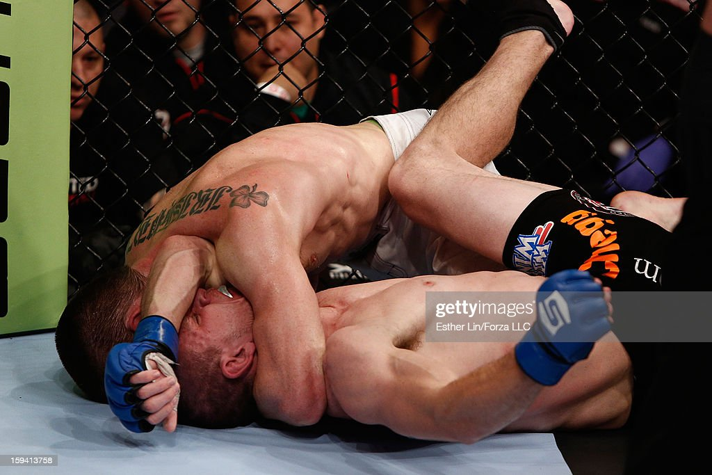 Pat Healy attempts an arm triangle choke submission against Kurt Holobaugh in their lightweight bout during the Strikeforce event on January 12, 2013 at Chesapeake Energy Arena in Oklahoma City, Oklahoma.
