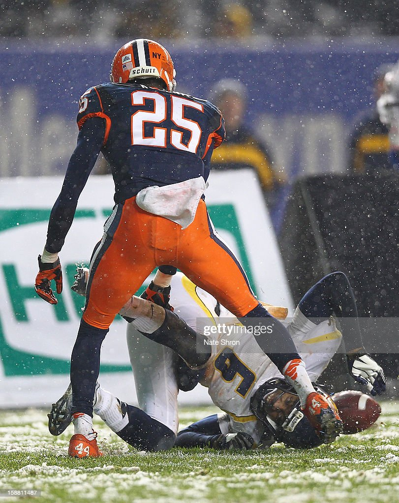 Pat Miller #6 of the West Virginia Mountaineers loses the ball against Jeremiah Kobena #25 of the Syracuse Orange during the New Era Pinstripe Bowl at Yankee Stadium on December 29, 2012 in the Bronx borough of New York City.