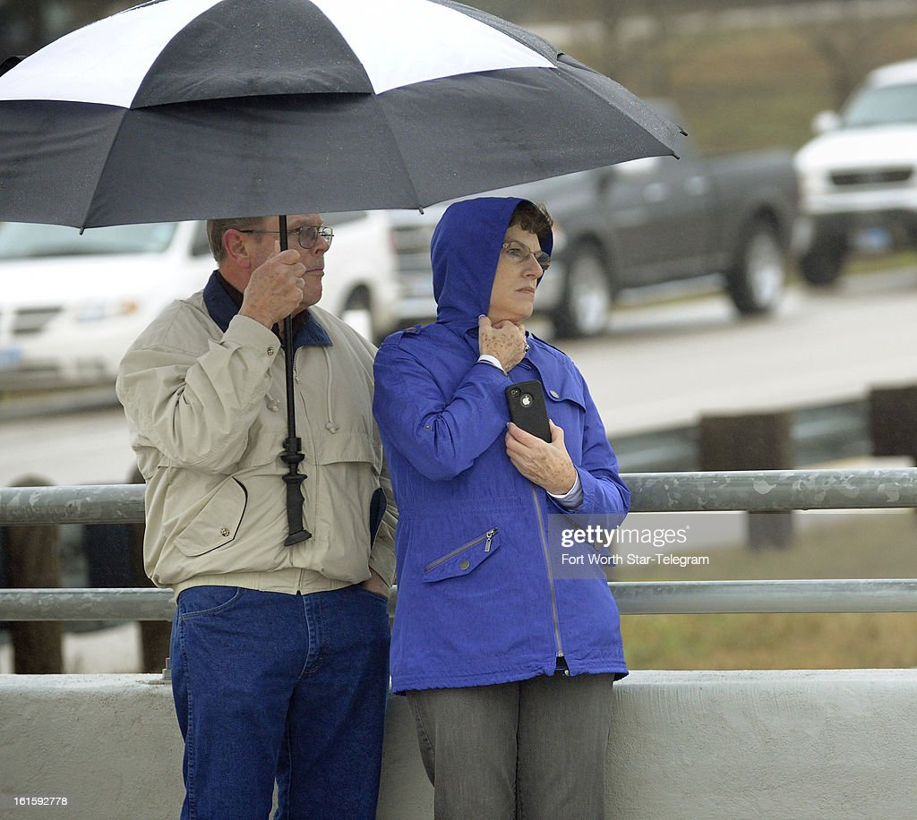 Pat Morrison, left, and Dianne Boyd, brave the cold and rain along US 287 to pay their respects to Chris Kyle in Midlothian, Texas, Tuesday, February 12, 2013. A motorcade of about 200 vehicles accompanied the white hearse carrying Kyle's flag-draped coffin on the 200-mile journey to Austin, where he will be buried at the Texas State Cemetery.